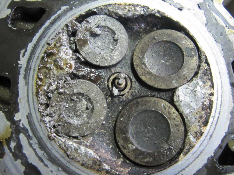 defekter Zylinderkopf mit eingearbeiteten Kolben-Stückchen